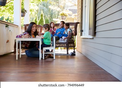 Family Sit On Porch Of House Reading Books And Playing Games