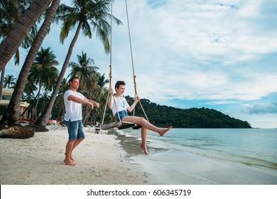 Family sit on Swing tropical beach