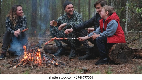 Family sits around a campfire on a summer evening. Children with parents are resting in the woods. Family frying sausages over a fire in the woods. Weekend in nature in good company.  - Shutterstock ID 1949777386