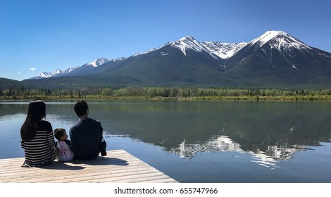 A family sits on a wooden pier beside Vermilion Lakes on the background of the Sundance Peak. Concept of vacation, relaxation, family, quality time.