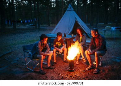 A family sits together at the camp fire at a campsite / Finland, scandinavia, europe