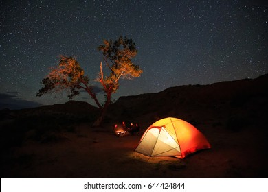 Family sitting around a campfire under the stars in the Utah desert, USA.