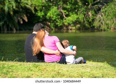 family sitting by the lake