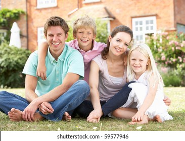 Family Sitting In Garden Together