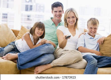 Family sitting in living room watching tv
