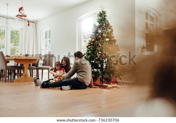 Family sitting near Christmas tree opening gift boxes. Young couple helping their daughter open Christmas gifts.