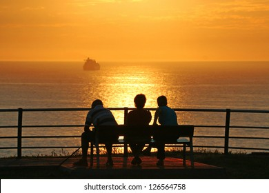 family sitting on a bench contemplating the sea