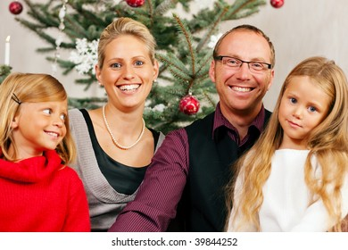 Family sitting on Christmas day in front of the Christmas tree, smiling