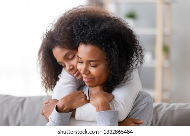 Family sitting on couch in living room at home african teenager daughter embracing from behind beloved mother. Relative people, older younger sisters, new mom for adopted child, love and care concept