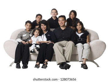 Family sitting on a couch smiling.
