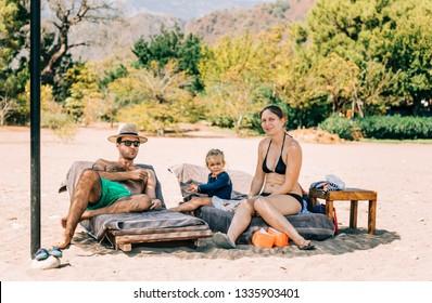 Family sitting on deck chairs at beach - Cirali, Antalya Province, Turkey