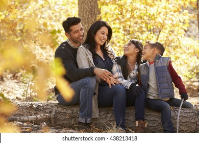 Family sitting on fallen tree in a forest look at each other