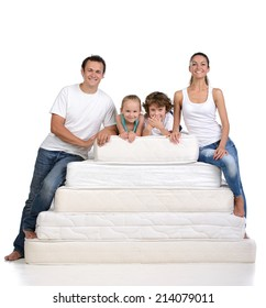 Family sitting on a large number of mattresses on white background