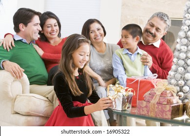 Family Sitting On Sofa In Front Of Christmas Presents,Young Girl Selecting A Gift