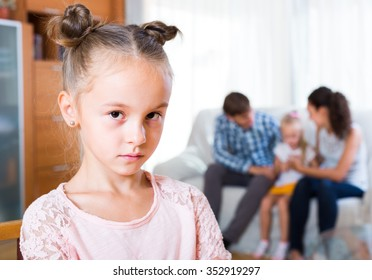 Family sitting on sofa and jealous sister standing apart