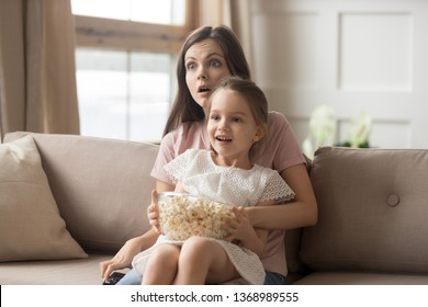 Family sitting on sofa in living room mother holds on lap little daughter watching movie eating pop-corn feels shocked astonished and amazed, sisters spends weekend together, amusement at home concept