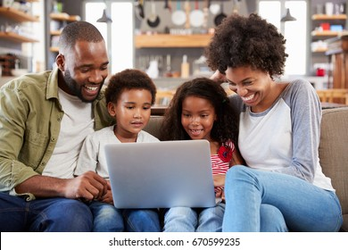 Family Sitting On Sofa In Open Plan Lounge Using Laptop