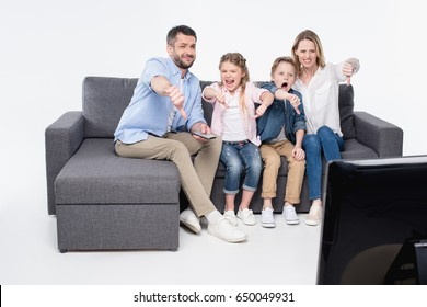 family sitting on sofa and showing thumbs down while watching tv together