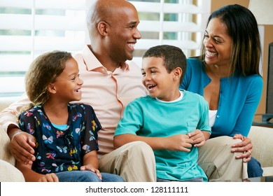 Family Sitting On Sofa Together