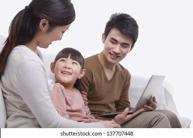 Family sitting on the sofa using laptop, mother looking at daughter, studio shot