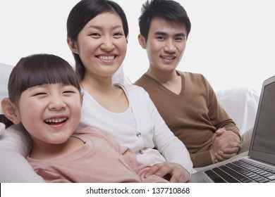 Family sitting on the sofa using laptop, looking at camera, studio shot