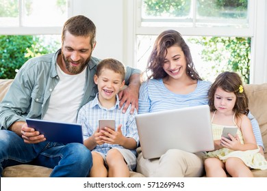 Family sitting on sofa and using a laptop, tablet and phone at home
