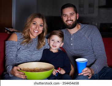 Family Sitting On Sofa Watching Television Together