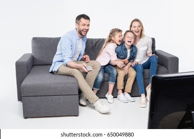 family sitting on sofa while watching tv and laughing together
