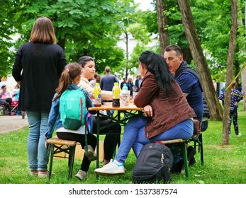 Family sitting at an outdoor table in the park having refreshing drinks in Cluj-Napoca, Romania on May 19, 2018.