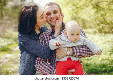 Family sitting in a park. Mother and father walking in a summer forest with little son. Couple with child