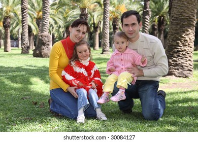 Family sitting at park with palm trees