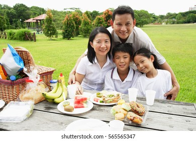 Family sitting at picnic table, looking at camera, portrait