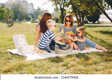 Family sitting in a summer park. Mother in a white t-shirt. Cute little boy and girl
