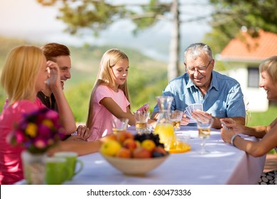 family sitting at table playing cards in nature
