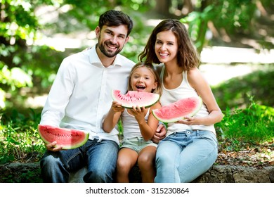 Family is sitting together in the park with watermelon. Sitting on the stone and smiling.