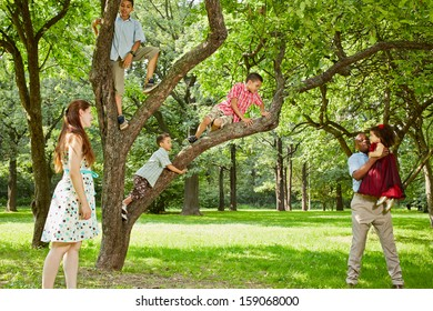 Family of six takes rest in park, boys climb on tree, father plays with little daughter, mother stands aside