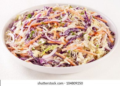 A family size bowl of healthy coleslaw, made with green and red cabbage, carrot, red onion and a dressing with mayonnaise and low fat yoghurt.