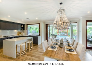 Family size dining area adjacent to the kitchen with an attached kitchen counter with a beautiful chandelier hanging over the dining table.