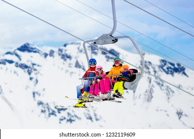 Family in ski lift in Swiss Alps mountains. Skiing with young kids. Father, mother and children sitting in ski lift during Christmas vacation. Winter outdoor sports for active family.