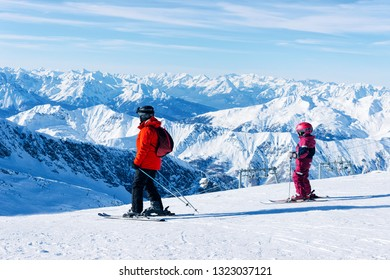 Family of Skiers at Hintertux Glacier ski resort in Zillertal, Tyrol. Austria in winter, Alps. People and Child at Alpine mountains with snow. Downhill fun. Blue sky and slopes. Hintertuxer Gletscher