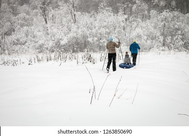 family skiing going through the winter forest in the snow