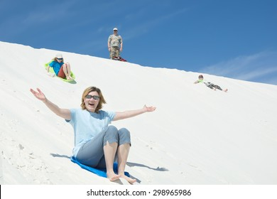 Family sledding, digging sand on a sand dune in White Sands National Monument, New Mexico