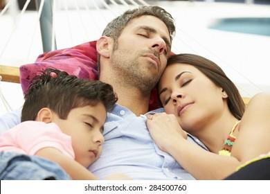Family Sleeping In Garden Hammock Together
