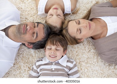 Family sleeping on floor at home with heads together
