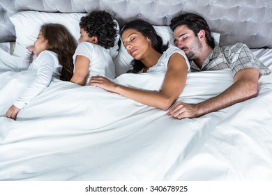 Family sleeping together in bed