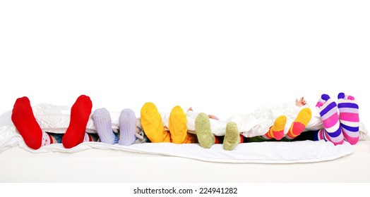 Family sleeping together. Feet of father, mother and four children in colorful knitted socks on white bed. Isolated on white background. Ready for your text