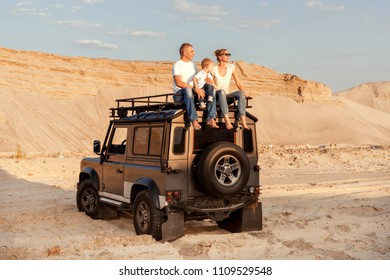 Family with a small child sit on the roof of the car, they travel through the desert among sand dunes.