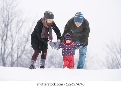 Family with a small child walk in the park in winter