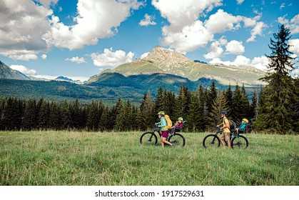 Family with small children cycling outdoors in summer nature, Tatra mountains Slovakia.