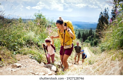 Family with small children hiking outdoors in summer nature, walking in High Tatras.
